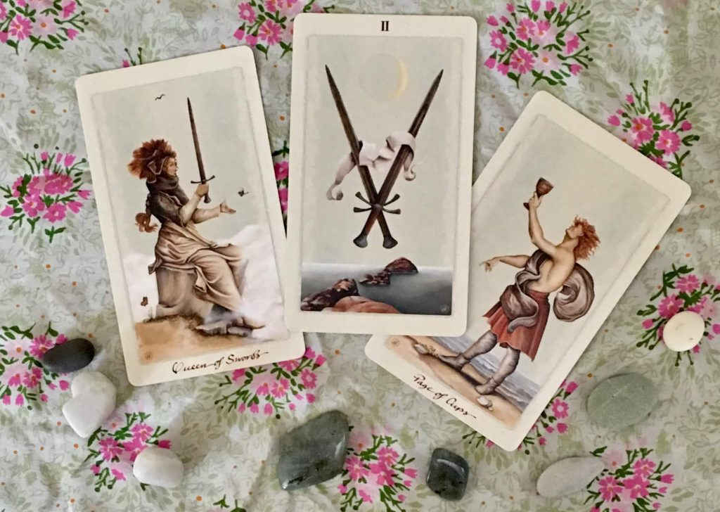 Three tarot cards: Queen of Swords, two of swords, page of cups, on a green floral background, with stones scattered around